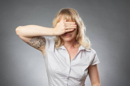 Young woman portrait on grey background, covering her eyes Stock Photo