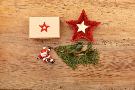wood figurine: Christmas present, fir twig and Santa Claus figurine on wood
