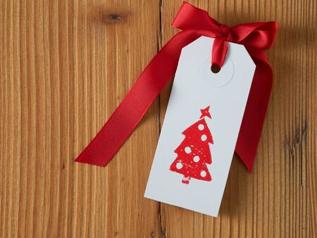 tag: Christmas, gift tag, printed, red ribbon, background wood Stock Photo
