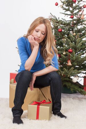 disappoint: adult woman sitting on gift with sad face Stock Photo