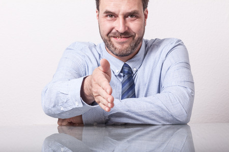reaching out: Business man reaching out for hand shake. Mature CaucasianEuropean adult, glass table with reflection.