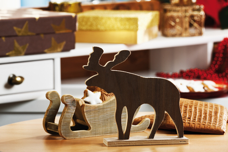 christmas elk: Christmas decoration, wooden elk figurine and tiny sledge with cookies on table