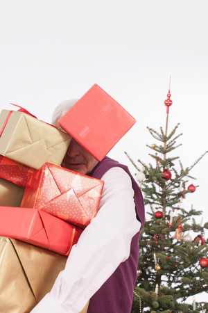 only senior adults: Senior man holding stack Christmas gifts