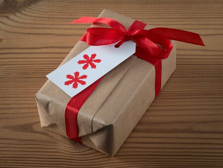 printed: Christmas present with gift tag, printed, red ribbon Stock Photo