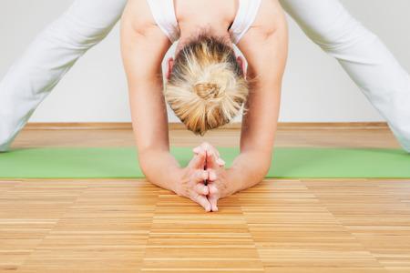 bending: Woman practicing Yoga, bending forward