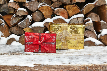 heap of snow: Christmas presents in front of woodpile