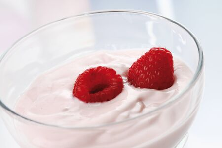 differential: Two raspberries and yogurt in glass bowl,close up