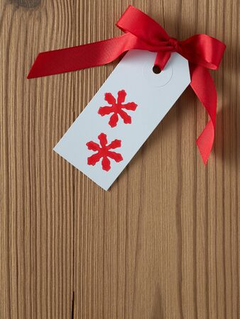 christmas gift tag: Christmas, gift tag, printed, red ribbon, background wood Stock Photo