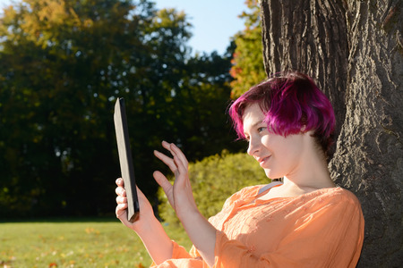 autumnally: Young woman with tablet computer in park Stock Photo