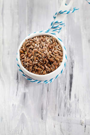 linum usitatissimum: Flax seeds (Linum usitatissimum) in small porcelain bowl Stock Photo