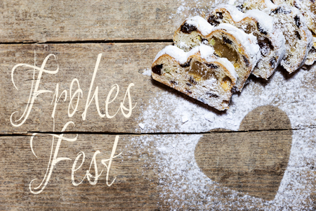 happy holidays: Stollen and heart of icing sugar on wood, happy holidays Stock Photo