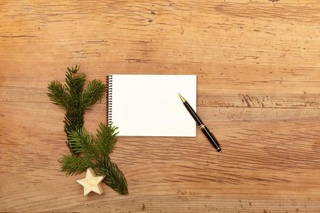 fir twig: Notepad and ballpen, fir twig on wood