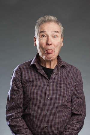 Älterer Mann streckt sterben Zunge heraus