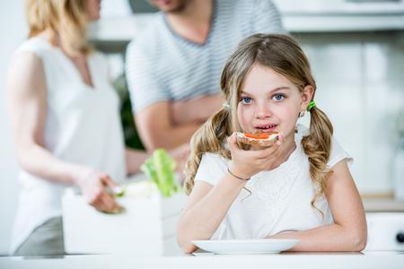 comiendo pan: Niña de comer pan con tomate y cebollino en la cocina