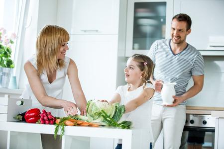 ni�os cocinando: Familia joven con las verduras frescas en la cocina