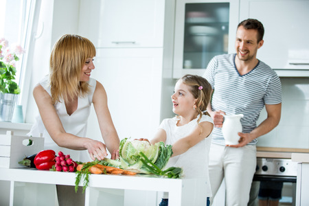mom and dad: Young family with fresh vegetables in kitchen Stock Photo