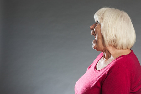 bonkers: Female senior profile view, screaming. Horizontal portrait on gray background with copy space Stock Photo