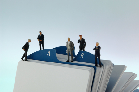 Business men figurines standing on alphabetical index card file Stock Photo