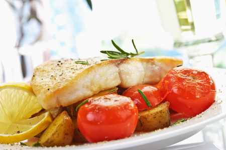 fish fillet: Victoria perch, fish fillet with grilled tomatoes, jacket potatoes on plate Stock Photo