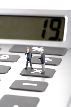 rising prices: Figurines standing on calculator