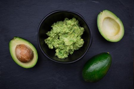 halved  half: Guacamole, Avocado cream in bowl, avocados