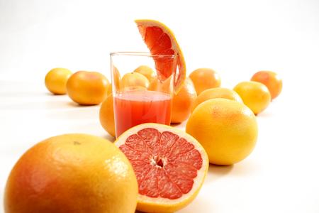 grapefruit juice: Grapefruit juice in glass, grapefruits, white background