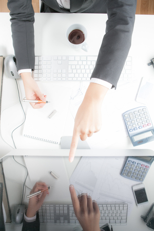 Woman working at desk, pointing on screen