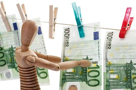 wood figurine: Wooden figurine, 100 Euro bank notes hanging on clothesline, close-up
