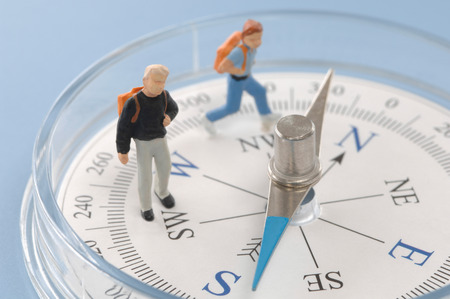 Pupil figurines placed on compass, close up Foto de archivo