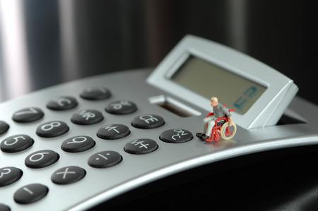 male likeness: Figurine in wheelchair on calculator keyboard