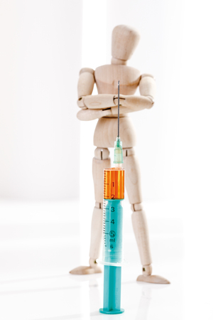 wood figurine: Wooden figurine and syringe, close-up