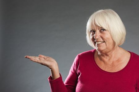 looking into camera: Female senior holding out hand, looking into camera. Horizontal portrait on gray background with copy space Stock Photo