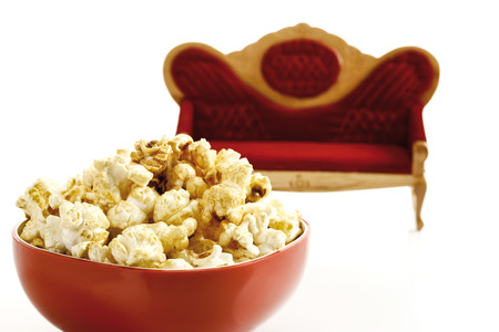 nibbling: Popcorn in bowl, sofa in background, close-up Stock Photo