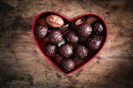 gifting: Chocolate truffles in heart shaped box on wood, valentine, mothers day present Stock Photo