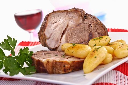 Rooled roast, pork with potatoes on plate, red wine glass