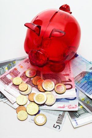 frugality: Red piggy bank with euro coins and banknotes