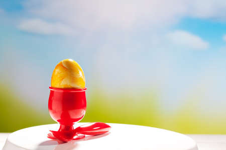 egg cup: Yellow Easter egg in red egg cup, Eastern