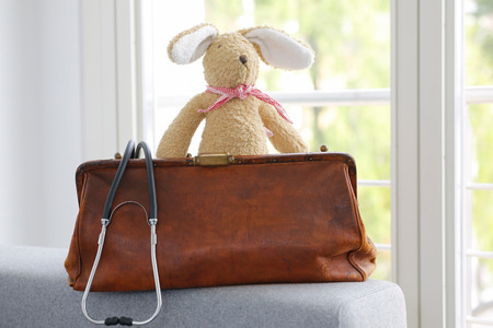 Old leather doctor bag and stethoscope, soft toy bunny