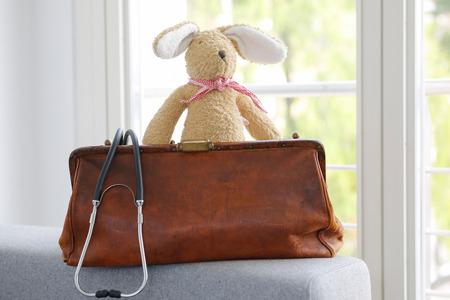 Oude lederen dokterstas en stethoscoop, zacht stuk speelgoed konijntje Stockfoto