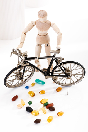wood figurine: Wooden figurine holding racing cycle, in foreground pills, elevated view Stock Photo