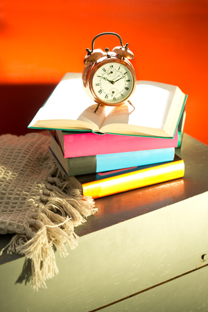 bedside: Bedtime reading, alarm clock and books on bedside table Stock Photo
