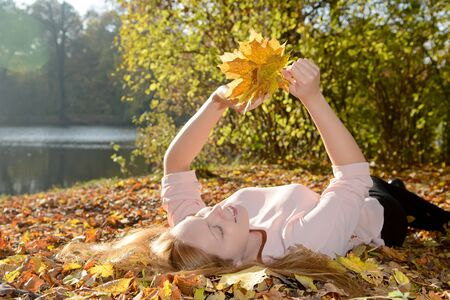 lying on leaves: Happy young woman lying on autumn leaves in park holding bunch of leaves