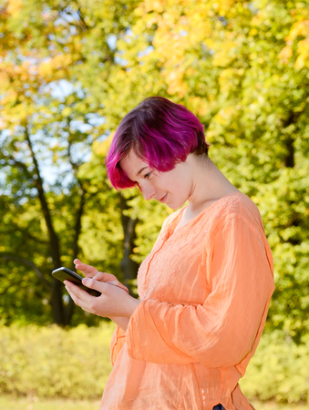 autumnally: Young woman with smartphone in park, autumn
