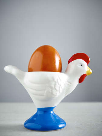 egg cup: Easter, egg cup, cock figurine on concrete Stock Photo