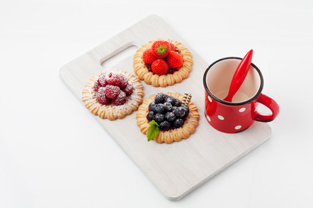cooky: Tartlets, raspberry, strawberry and blueberries, coffee cup Stock Photo