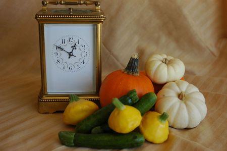 sqush and pumpkins beside a travel clock Stock fotó