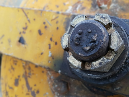grease: Yellow concrete mixers lock nut with rust and grease