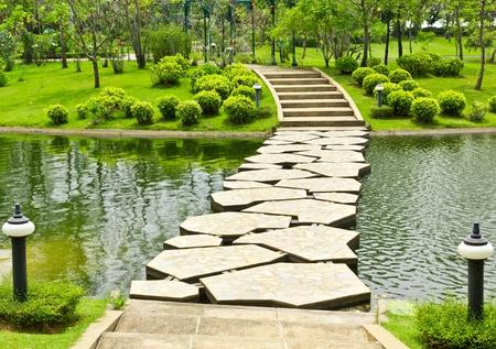 stenen loopbrug op het water in het park