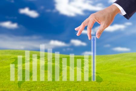 Business Man Hand holen oben im Diagramm in blauer Himmel Standard-Bild