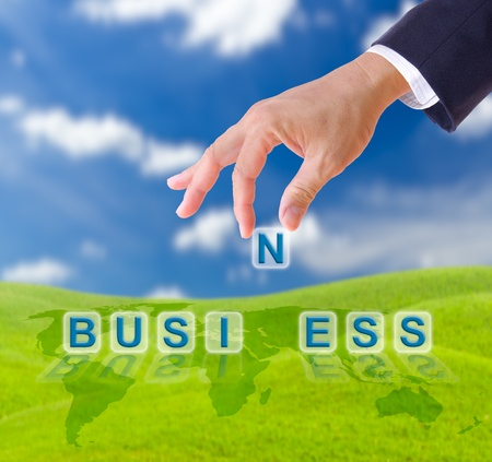 business man hand and business word on blue sky photo
